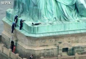 Mujer escala la Estatua de la Libertad