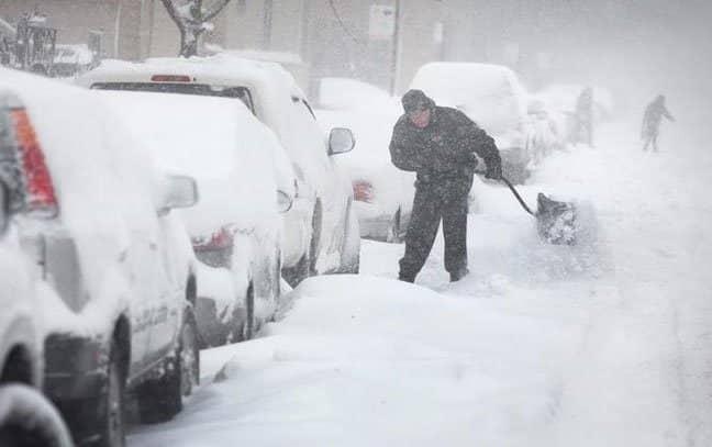 Un hombre con una pala quita nieve de las calles de ny